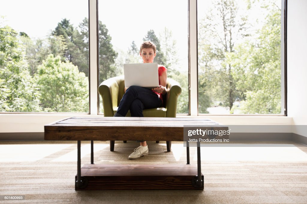 Caucasian businesswoman using laptop in empty office