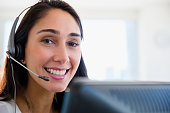 Caucasian businesswoman wearing headset at desk