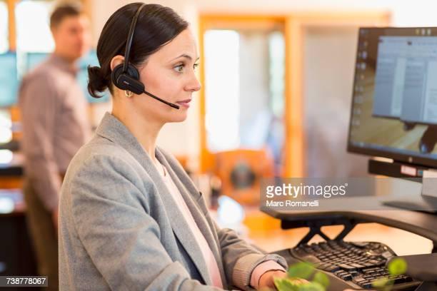Caucasian businesswoman wearing headset using computer