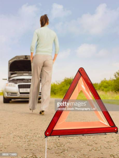 Caucasian businesswoman with warning sign near broken down car on rural road