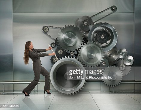 Caucasian businesswoman working metal cogs