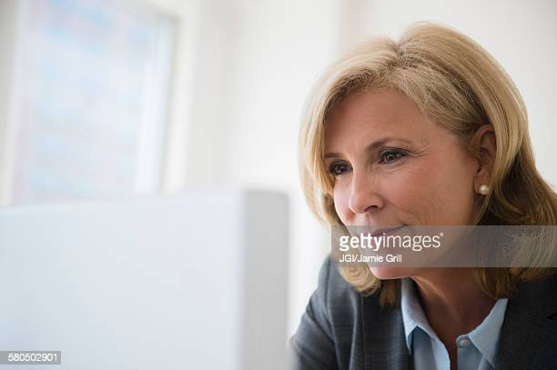 Caucasian businesswoman working on computer in office