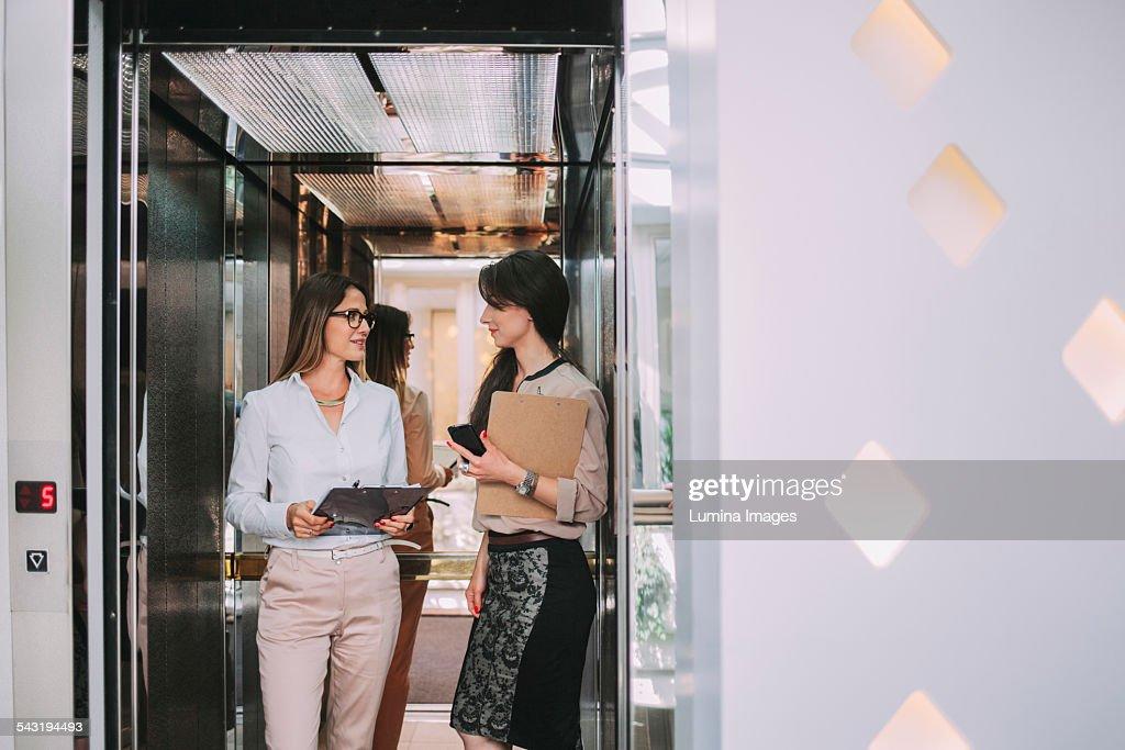 people talking in elevator. caucasian businesswomen talking in elevator people