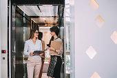 Caucasian businesswomen talking in elevator