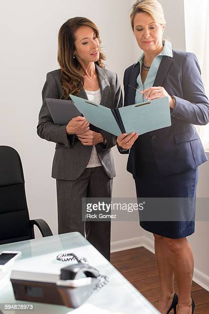 Caucasian businesswomen talking in office