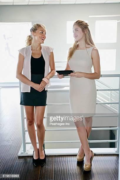 Caucasian businesswomen talking near staircase