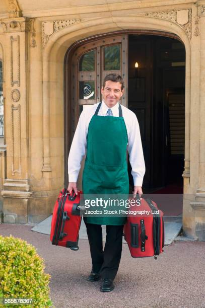 Caucasian butler carrying luggage outside hotel