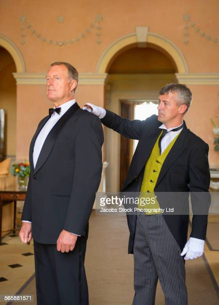 Caucasian butler dusting jacket of man in mansion parlor