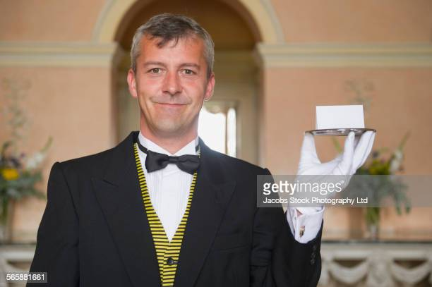 Caucasian butler holding business card on serving tray