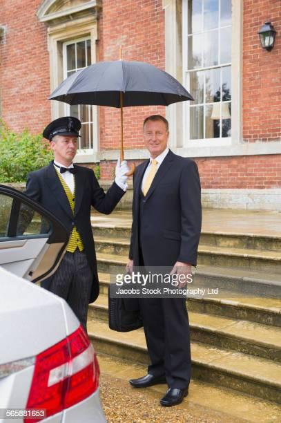 Caucasian butler holding umbrella for businessman outside car