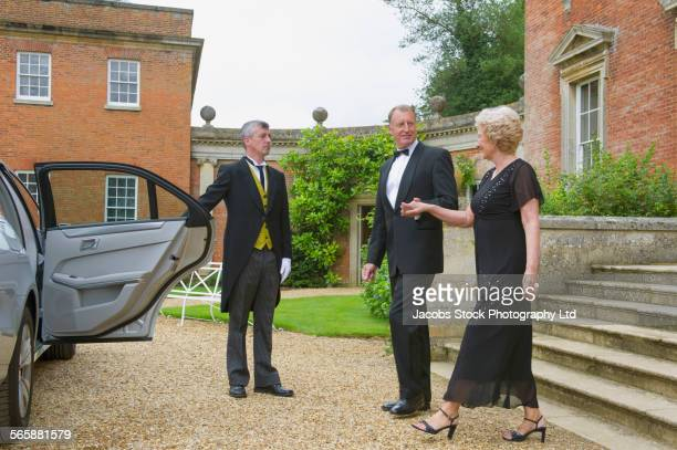 Caucasian butler opening car door for couple outside mansion