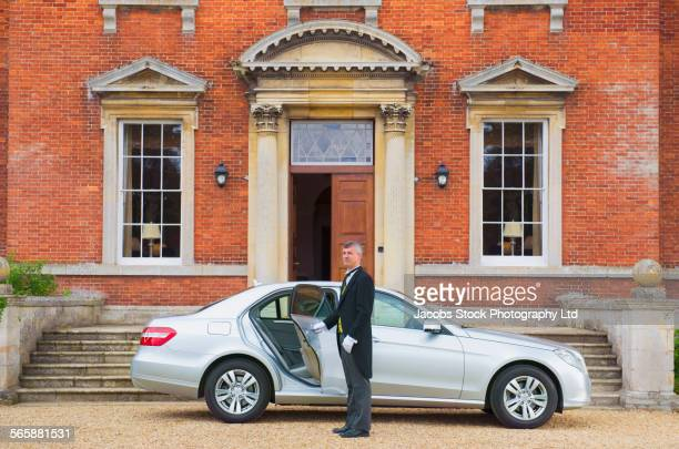 Caucasian butler opening car door outside mansion