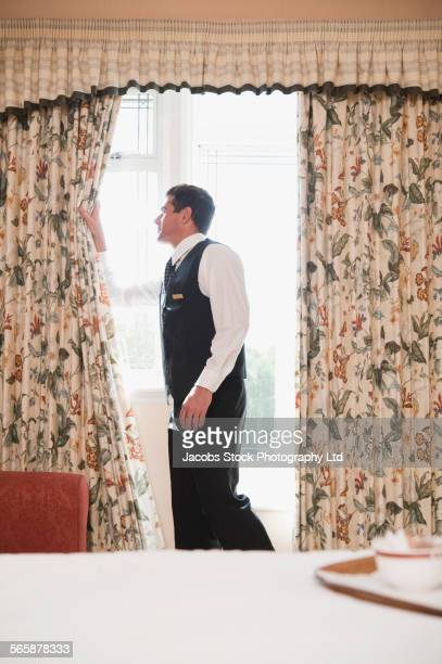 Caucasian butler opening curtains in hotel room