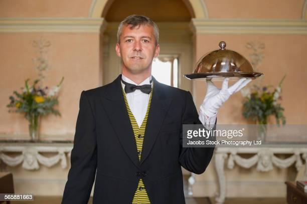 Caucasian butler serving food on platter