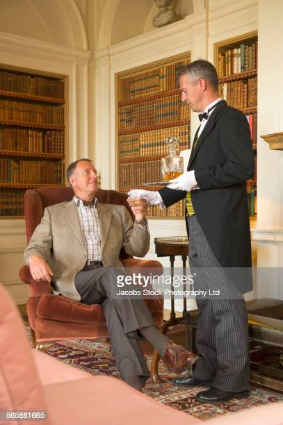 Caucasian butler serving man drink in library
