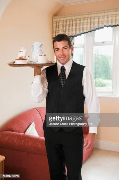 Caucasian butler serving tea in hotel room