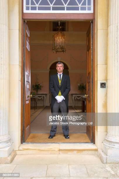 Caucasian butler standing at mansion front door