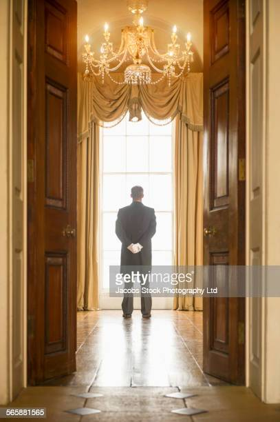 Caucasian butler standing at window in mansion