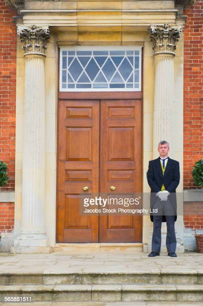 Caucasian butler standing outside mansion front door