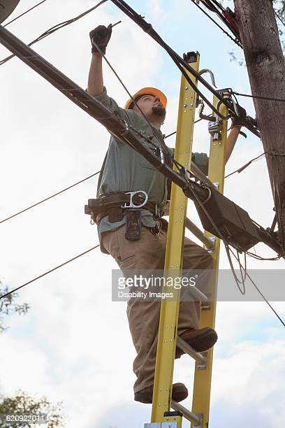 Caucasian cable installer working on ladder