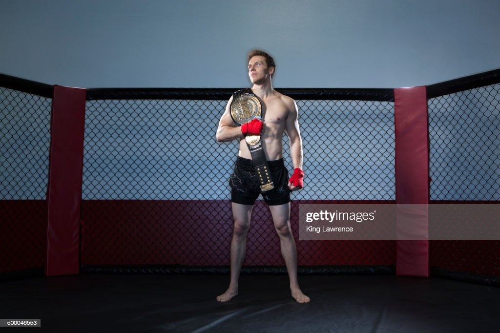 Caucasian cage fighter holding championship belt