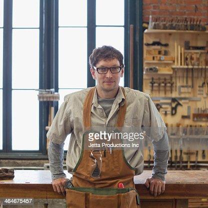 Caucasian carpenter smiling in workshop
