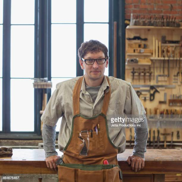 Caucasian carpenter smiling in workshop