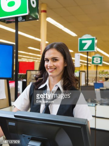 Caucasian cashier at grocery store checkout : Stock Photo