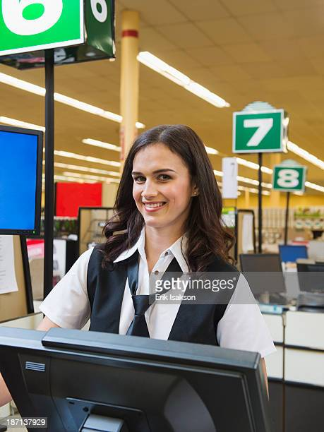 Caucasian cashier at grocery store checkout