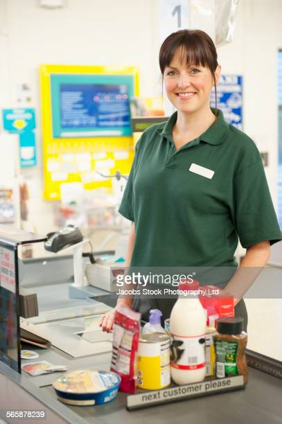 Caucasian cashier working at grocery store checkout
