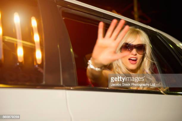 Caucasian celebrity greeting paparazzi from limousine window