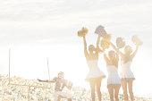 Caucasian cheerleaders on sidelines at football game