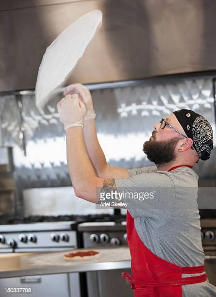 Caucasian chef preparing pizza in kitchen