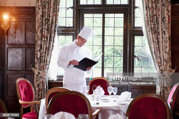 Caucasian chef reading menu in empty restaurant
