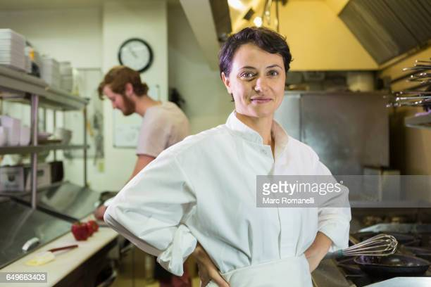 Caucasian chef smiling in restaurant kitchen