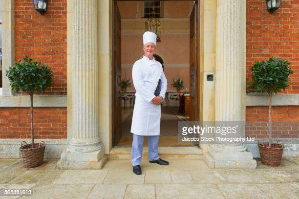 Caucasian chef standing in mansion front door