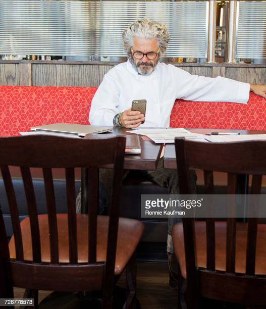 Caucasian chef texting on cell phone in restaurant