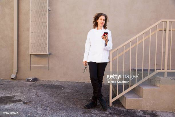 Caucasian chef texting on cell phone near staircase