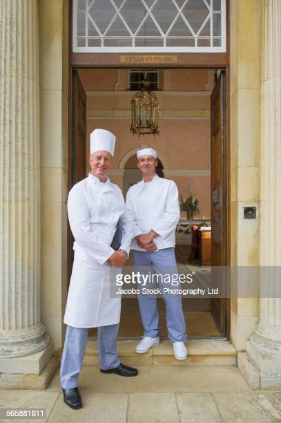 Caucasian chefs standing in mansion front door