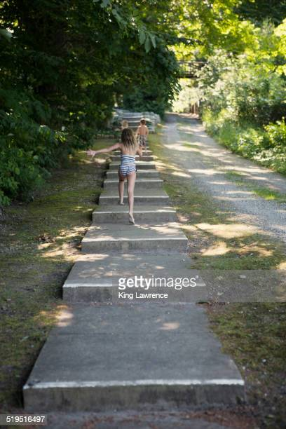 Caucasian children climbing stairs near rural path