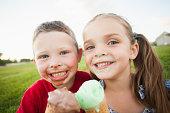 Caucasian children eating ice cream outdoors