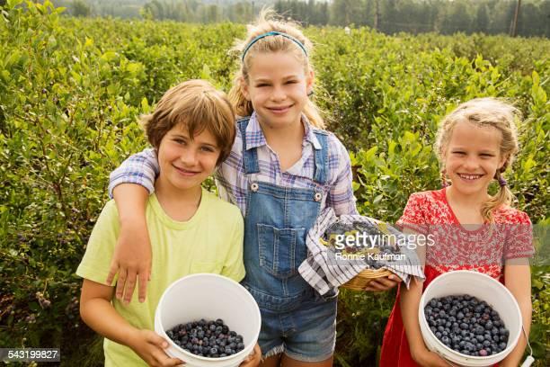 Caucasian children holding baskets of blueberries on farm