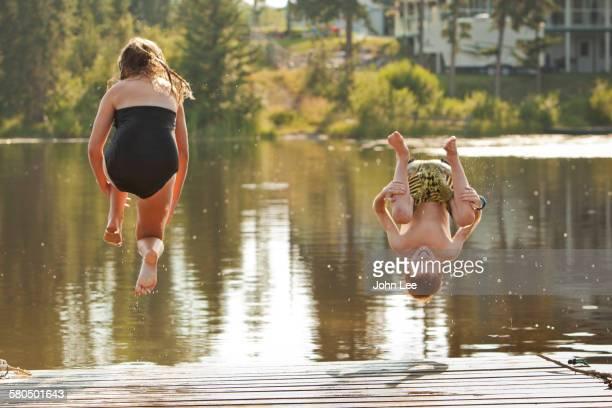 Caucasian children jumping into lake