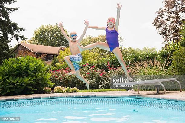 Caucasian children jumping into swimming pool