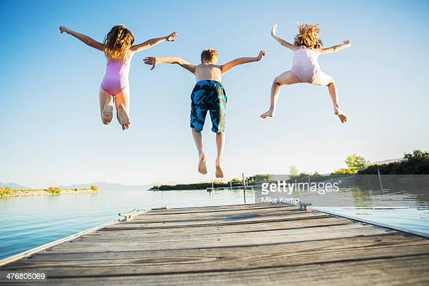 Caucasian children jumping off dock into lake