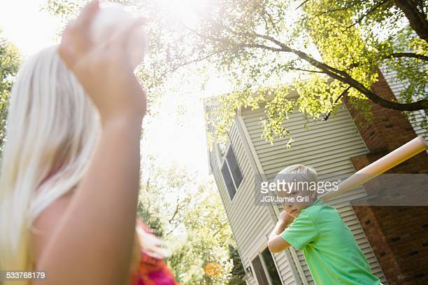 Caucasian children playing baseball in backyard