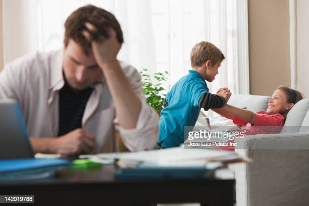 Caucasian children playing on sofa while father works