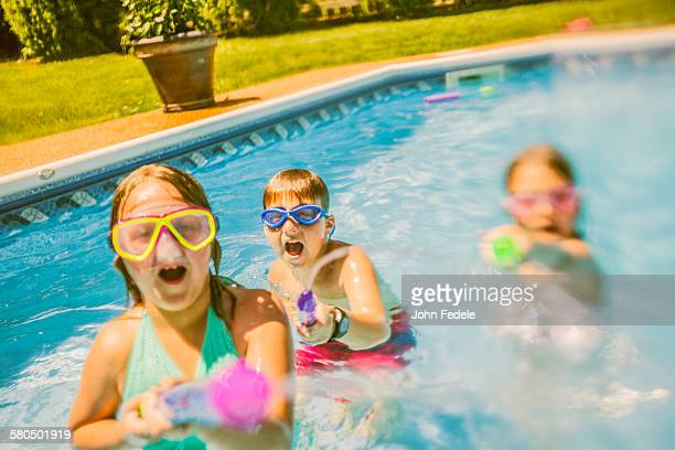 Caucasian children playing with squirt guns in swimming pool