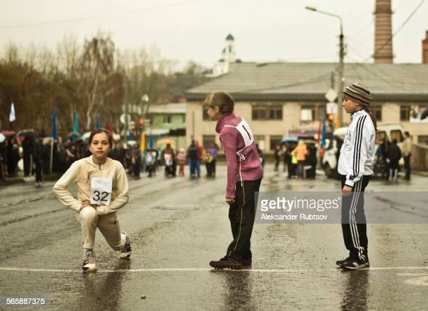 Caucasian children preparing for race on street