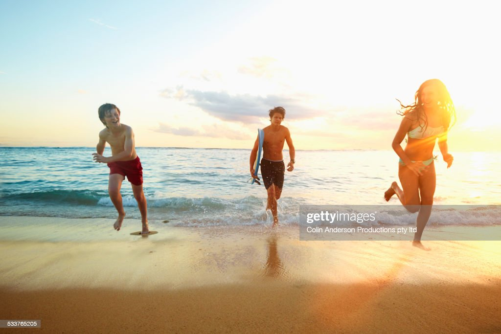 Caucasian children running from ocean on beach